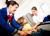 stock photo of seatbelt  - Air hostess helping a kid to fasten his seatbelt - JPG