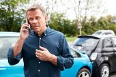 Mature Male Motorist Involved In Car Accident Calling Insurance Company Or Recovery Service poster