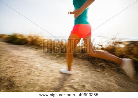 Young woman on her evening jog along the seacoast (motion blurred image)