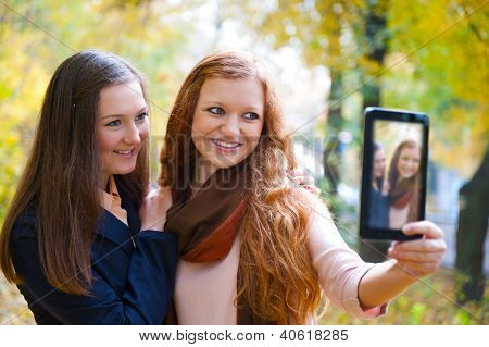 Duas meninas tirando foto com Tablet Digital