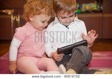 Duas crianças Cute brincando com Tablet