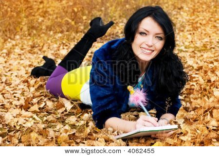 Pretty Girl In The Park With A Pen And A Note Book