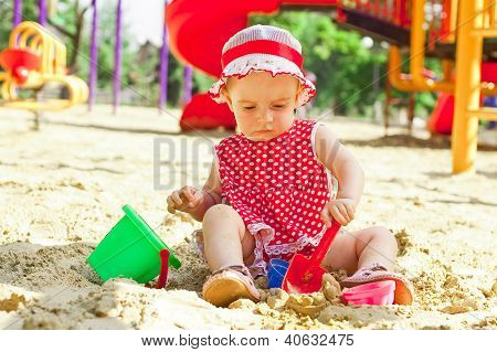 Beautiful Little Girl In Red Clothes, Playing In A Sandbox