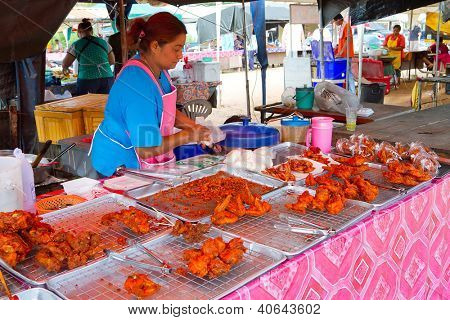 KHAO LAK, THAILAND - NOV 05: Unidentified woman selling prepared food on the local market in Khao Lak. This market is also tourist attraction in Phang Nga province, Thailand on Nov.05, 2012.
