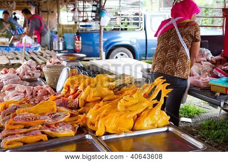 KHAO LAK, THAILAND - NOV 05: Unidentified woman selling chicken meat on the local market in Khao Lak. This market is also tourist attraction in Phang Nga province, Thailand on Nov.05, 2012.