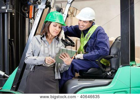 Female supervisor and forklift driver using digital tablet at warehouse