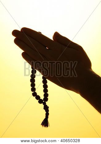 male hands with rosary, on yellow background