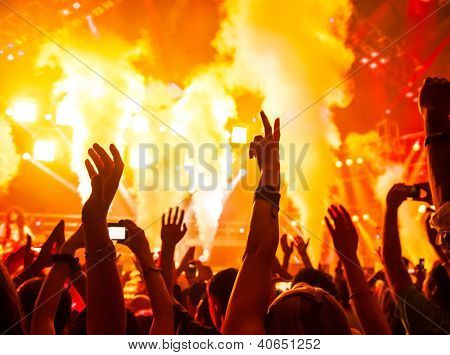 Photo of rock concert, music festival, New Year eve celebration, party in nightclub, dance floor, disco club, many people standing with raised hands up and clapping, happiness and night life concept
