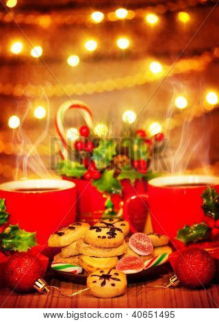 Picture of Christmas sweets, traditional Christmastime gingerbread with candy cane on festive table, two red cup for tea decorated with shiny bauble, tasty homemade cookies, New Year eve