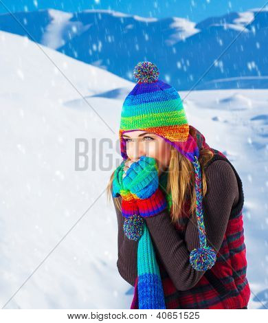 Picture of cute female in winter mountains, snowfall outdoors, beautiful woman wearing colorful wool hat, scarf and gloves, woman froze outdoor in cold snowy weather, wintertime holidays