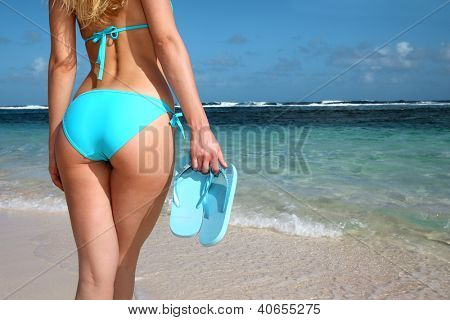 Back view of woman holding flipflops in hand