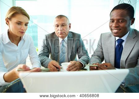 Portrait of business partners looking at laptop screen while female explaining something to her boss and colleague