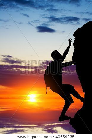 Silhouette Of A Person Without Insurance Climbs The Rock