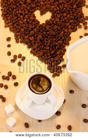 A cup of strong coffee and sweet cream on wooden table close-up