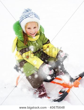 Smiling Happy litte girl with children's snowmobile