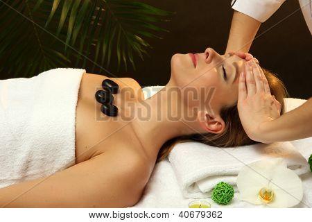 Retrato de uma mulher bonita com pedras spa massagem na cabeça de tomar