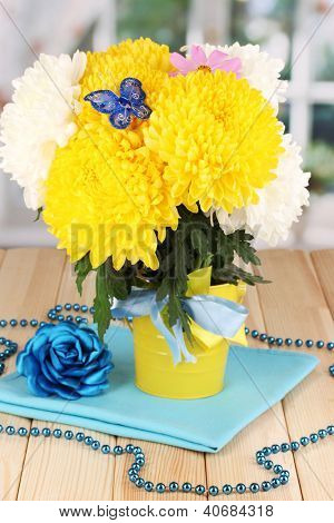 Beautiful chrysanthemum in pail on wooden table on window background