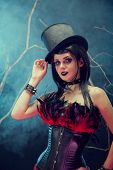 Attractive smiling gothic girl in tophat and feather corset, studio shot with fog and branches
