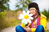 Funny girl in cap with ear flaps and flower