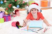 Little boy in Santa hat writes letter to Santa Claus