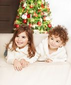 Photo of adorable kids, boy and girl laying down on the sofa and laughing, family at home celebrate