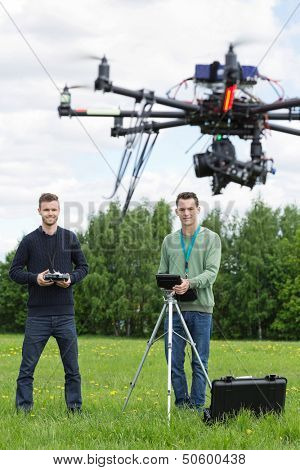 Young technicians flying UAV helicopter with remote control in park