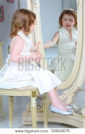 A little girl dressed admires her reflection in the large mirror