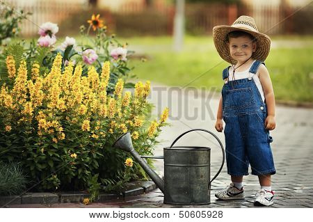little boy watering flowers watering can