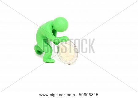 small green plasticine puppet rolls a coin