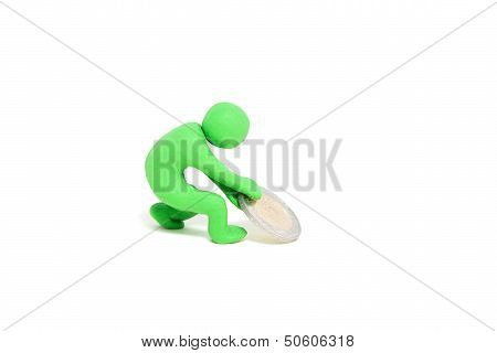 small green plasticine puppet pulls a coin