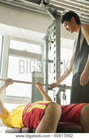 Young men weight lifting with his personal trainer in the gym