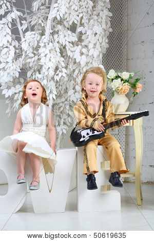 A little girl in white dress and pop musician with guitar sit on letters love and sing a song