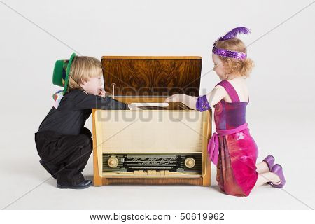 Little boy and girl sitting on the floor and play with the old radiogramophone