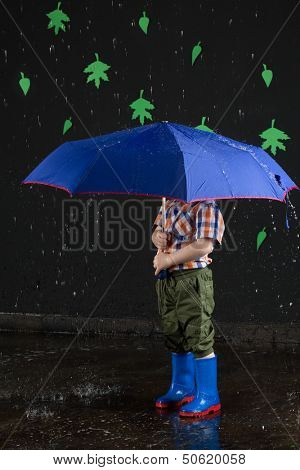 The little boy hid his head under a blue umbrella on a background of black wall with leaves