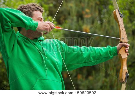Man in green jumper about to shoot arrow at the archery range