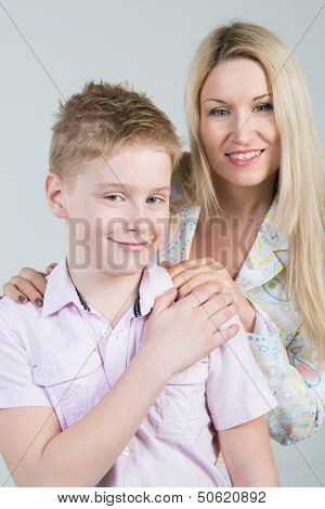 Happy mother hugging smiling son in pink shirt with disheveled hair in the studio