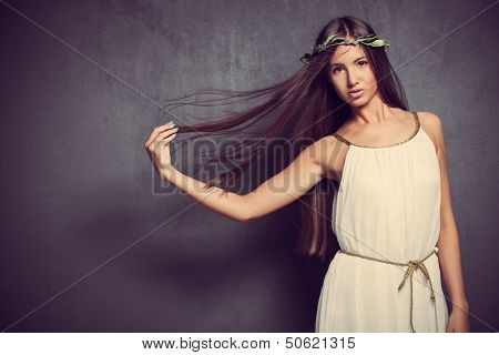 natural looking young woman with long straight hair in white simply  dress  and wreath of leaves in hair studio shot