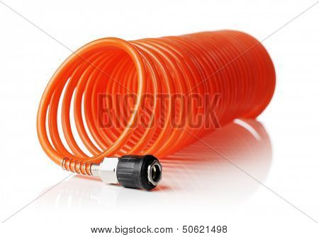 Orange red thin spiral air hose used for pneumatic tools. Isolated on white with natural reflection. Very short depth-of field, the sharpness is in the connector.
