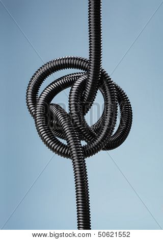 Tangled black flexible air hose.
