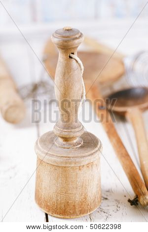 retro kitchen utensils  masher on old wooden table in rustic style