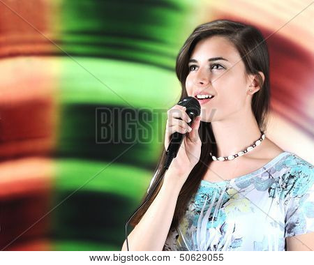 A beautiful teen soloist happily singing into her microphone with plenty of space for your text on her left.