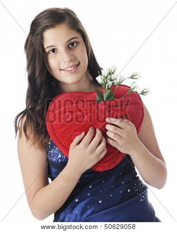An attractive young teen in formal wear happily holding a red, heart-shaped pillow with a pocket full of white rose buds.  On a white background.