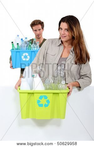 Couple recycling boxes of plastic bottles