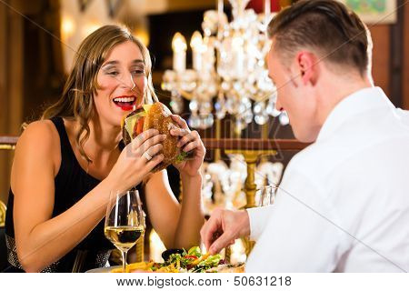 Couple - man and woman - in a fine dining restaurant they eat fast food, burger and fries - a large chandelier is in Background