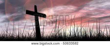 Concept conceptual black cross or religion symbol silhouette in grass over a sunset or sunrise sky with sunlight clouds background banner