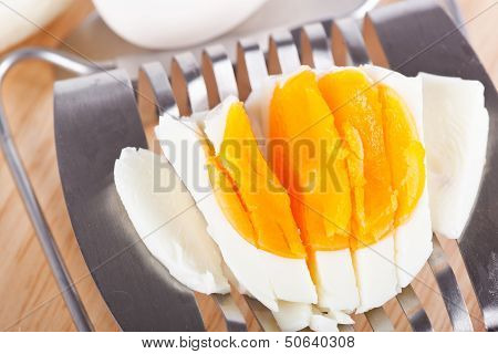 Egg Cutter And Cutted Eggs On Wooden Board