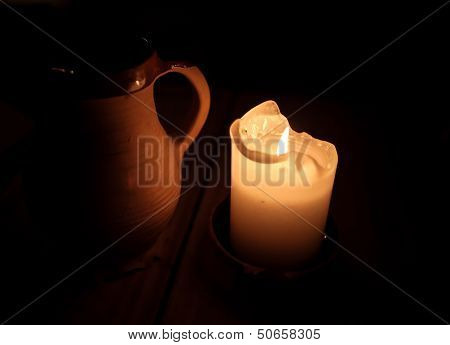 Burning Candle And Clay Cup Of Beer On Table In Old Restaurant