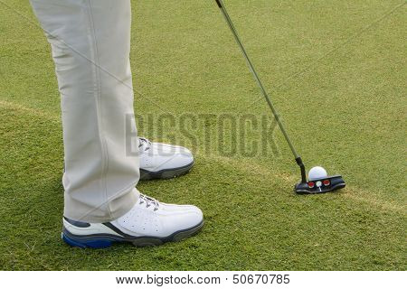 Closeup Of Legs With Golf Club And Ball On Tee Grass, Golfer Prepares To Putt