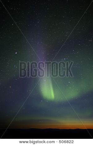 Green-purple Streak Of Aurora Over Twilight Horizon. Many Stars