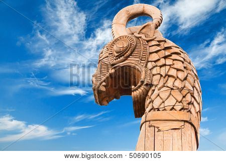 Carved Wooden Dragon On Forepart Of The Ancient Viking Ship Above Dramatic Blue Sky